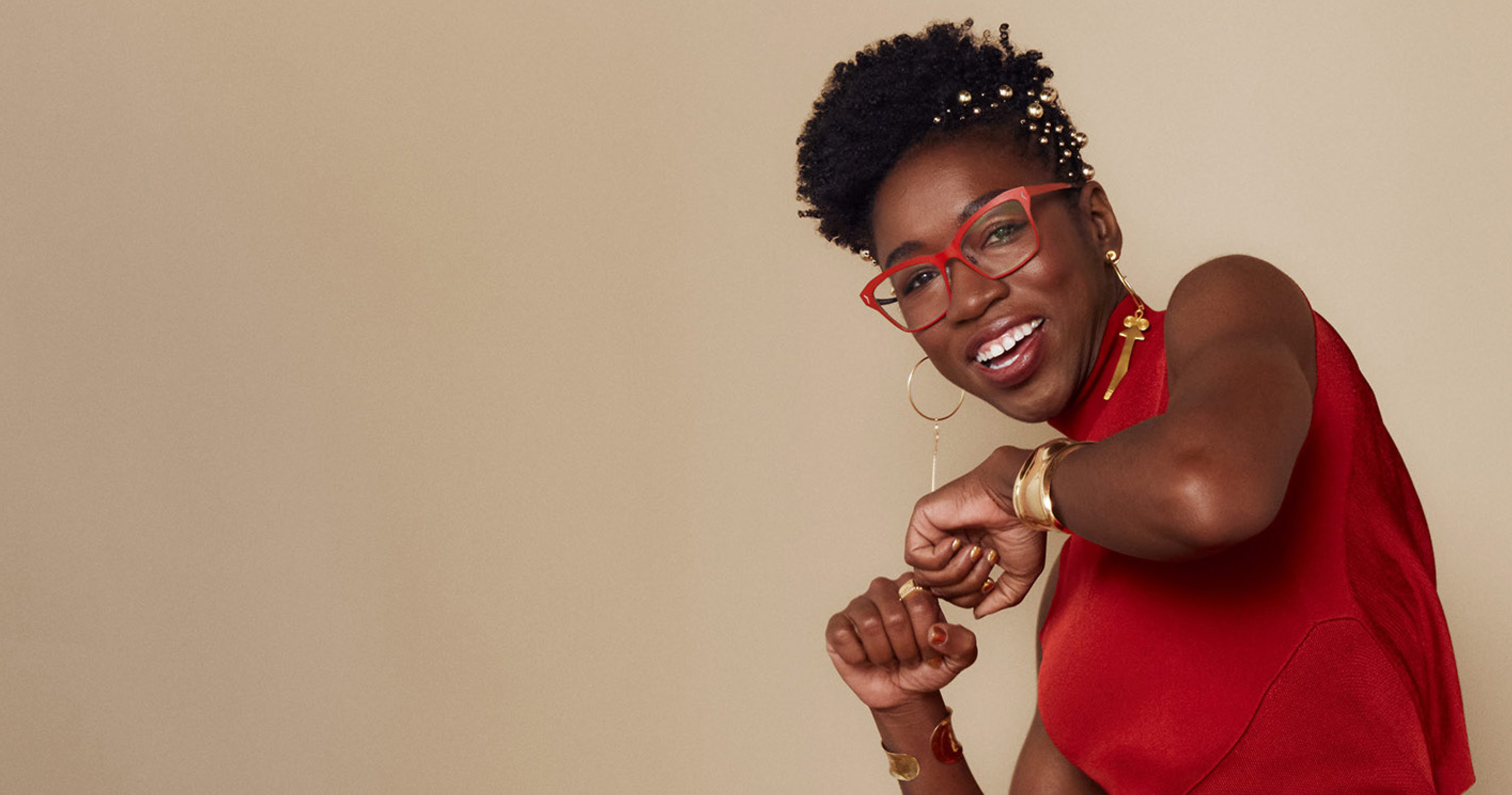 Joy Buolamwini in a red dress smiles and makes a punching motion.