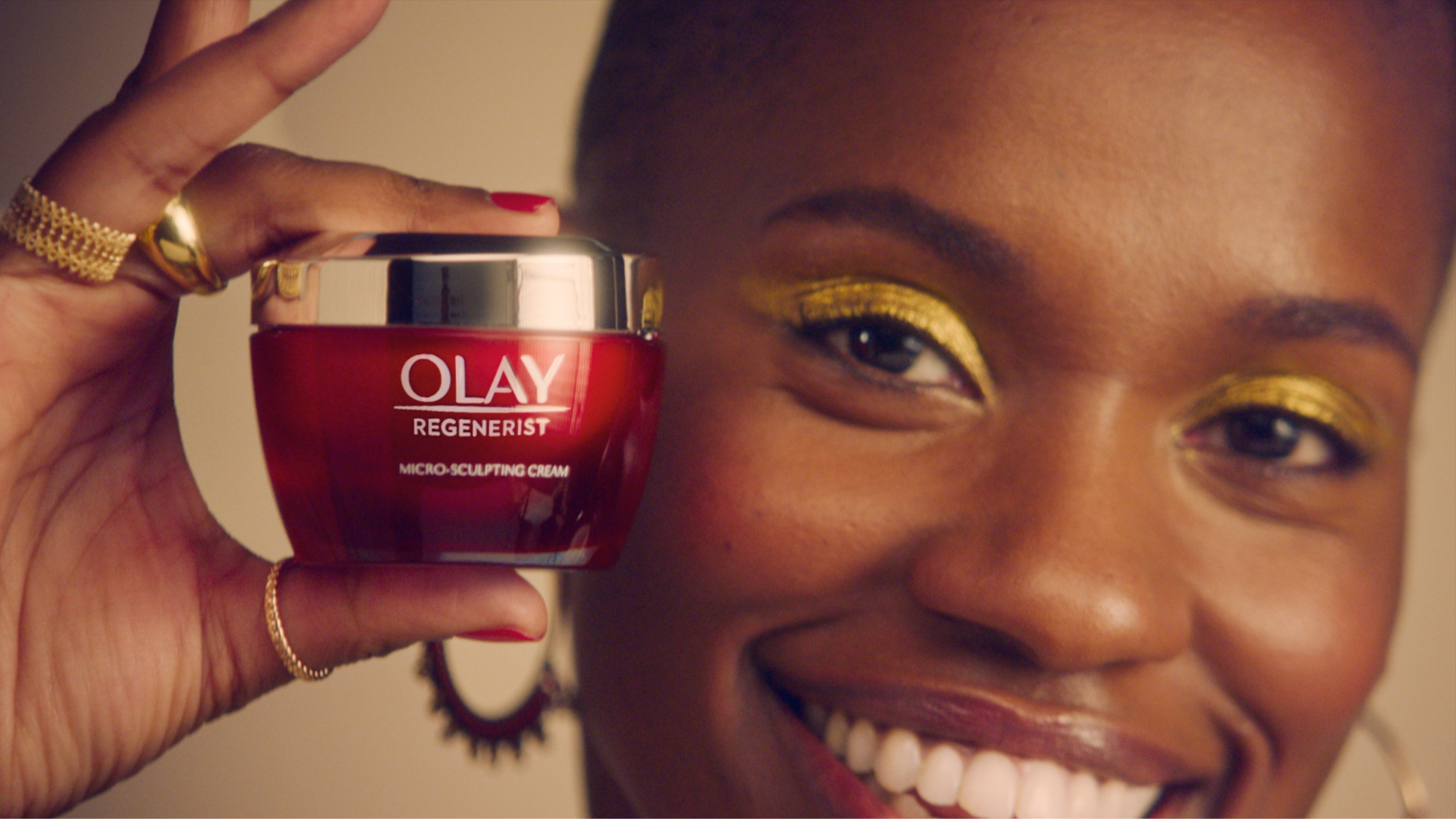 A black woman holds an Olay Red Jar up to her face. She is smiling.