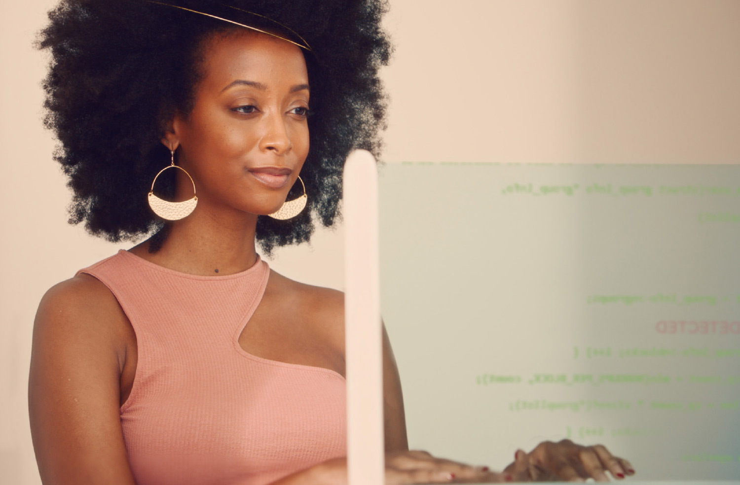 A black woman with a large afro sits behind a computer screen. Computer code is seen on the screen.