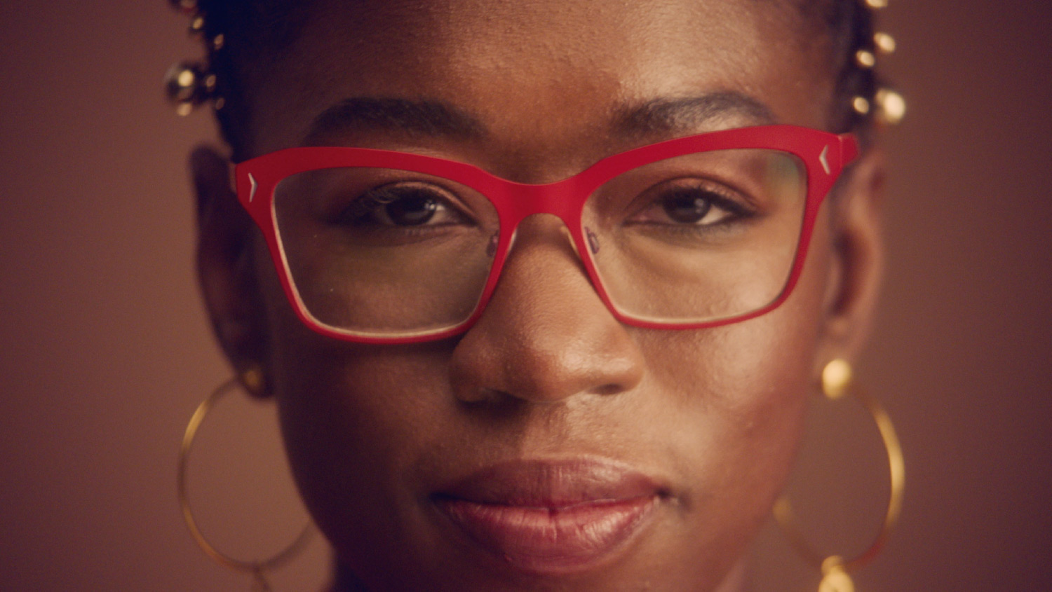 Joy Buolamwini staring straight on passionately. She is wearing red reading glasses with gold earrings.