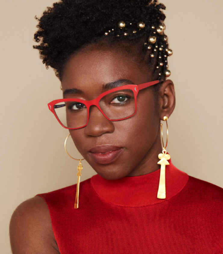 Portrait of Joy Buolamwini, an artificial intelligence researcher. She is wearing red reading glasses with gold earrings in a red dress.