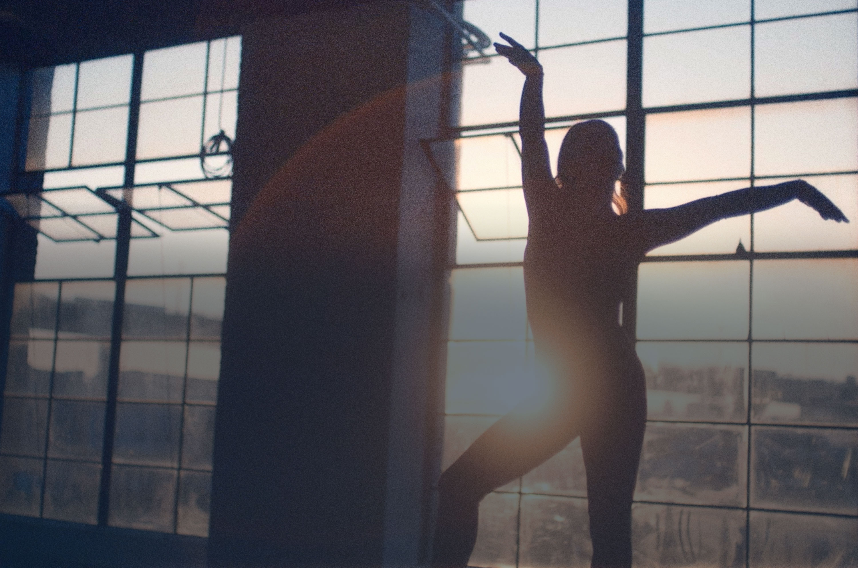 Aly practicing floor gymnastics silhouetted against a sunny window