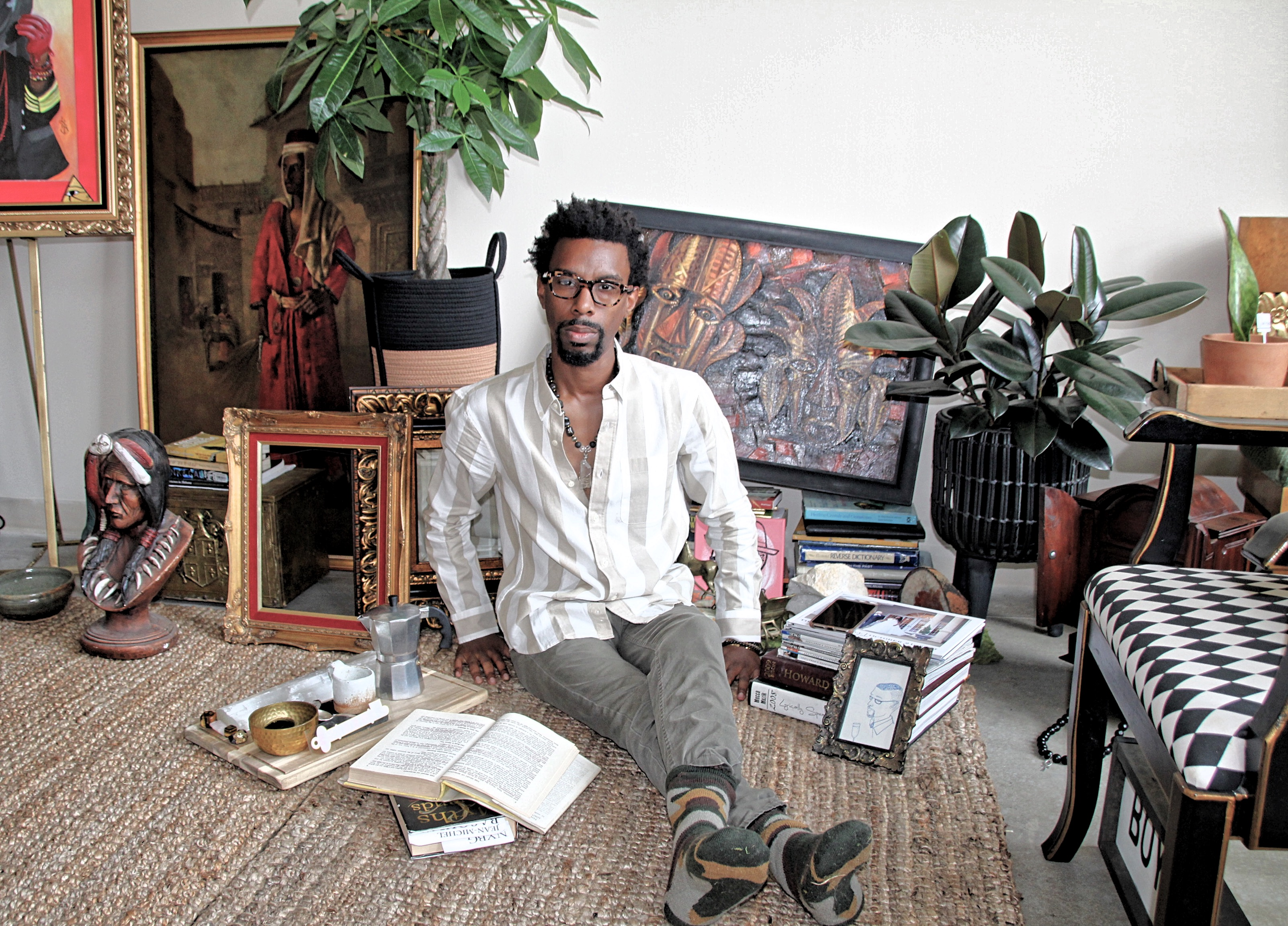 boybeads-new-york-sebastian-mitchell-tarver-sitting-in-loft-reading-books-with-coffee-and-crystals-on-jute-rug-african-american-black-man-sitting-on-rug-image.jpg