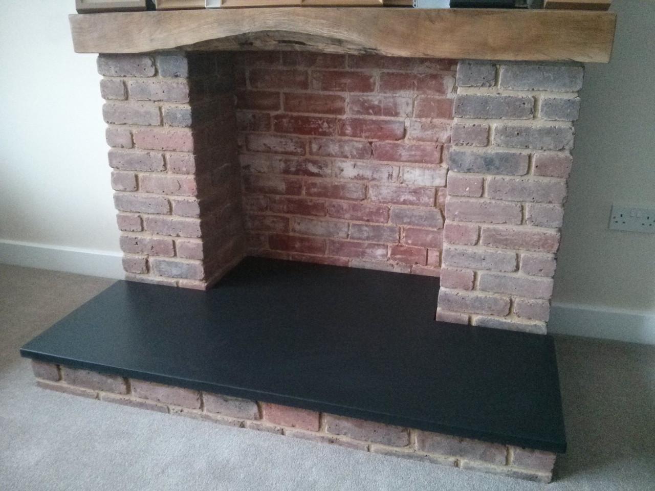 Honed black slate fireplace hearth around brick fireplace.