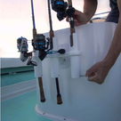 SeaSucker Pro Series 3-Rod Holder with 3 fishing rods in holder mounted on a fibreglass box in the boat