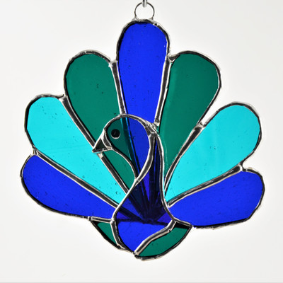 Peacock art glass suncatcher in blues and greens