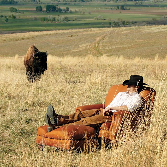 Cowboy sitting in chair in a field with bison