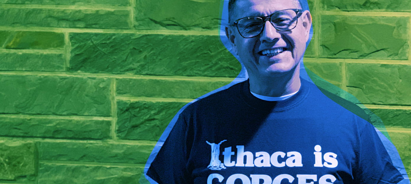 Omar Arango portrait, colored green & blue, wearing a Ithaca is Gorges t-shirt standing against a stone brick wall