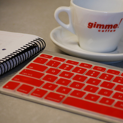 Keyboard with red buttons next to a Gimme-branded cup