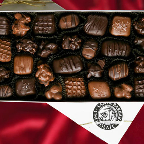 Chocolate covered nuts and caramels in a gift box. Chocolate gift box filled with assorted nuts and fruit.  Chocolate dipped nut clusters like almond and walnut clusters. Fruits like cranberries and raisins dipped in milk and dark chocolate.