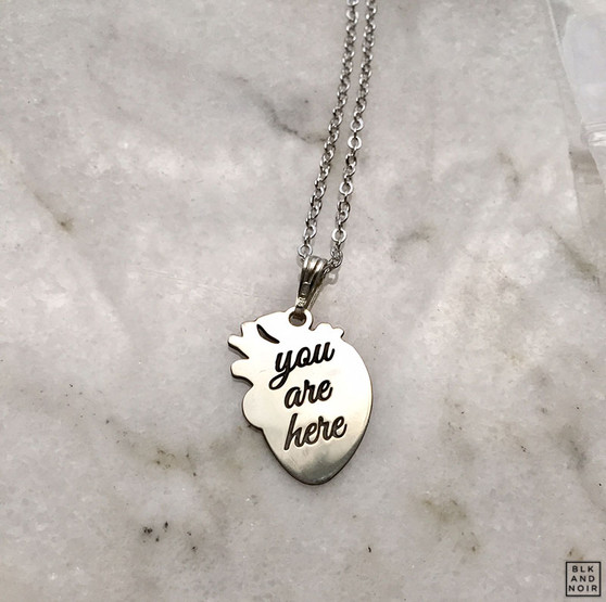 """You are here"" Human Heart Necklace in Rhodium Plated Silver."