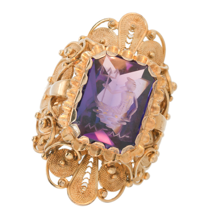 Light Shining through an Antique, Carved Amethyst and Gold Ring