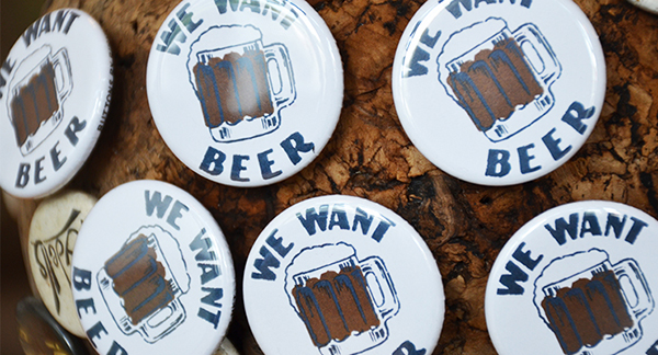 We Want Beer Buttons on a Cork Board