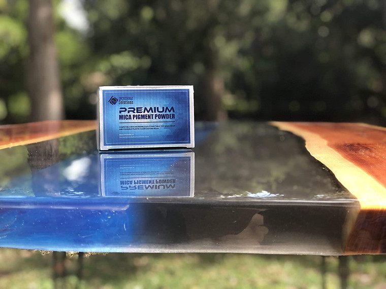 Premium Mica Pigment Powder by Incredible Solutions box sitting on a river table.
