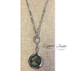 """Stainless steel, 16 inch chain included with this Moldavite capsulated pendant.  Moldavite will supercharge and spiritualize the energies of whatever stone one uses with it. Exposure to the Moldavite begins a process of energetic resonance in which the vibratory rate of our entire being is increased, which is why this is such a transformative gemstone. This stone or Tektite is said to be a meteorite that fell in the Chez Republic. As it landed the heat and the pressure of the meteor united with the earth and formed a glass-like stone with cosmic powers. Scientist could not duplicate this stone because there is nothing like it on our Earthly plane. Most people feel the stones vibe instantly when they hold a piece. Moldavite can also give you a out of body experience. Many people claim they leave their physical bodies and take a """"trip""""! Copyright © DeMarco,J. (2019) High Vibes Crystal Healing. Florida: Llewellyn Publishing"""