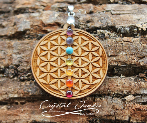 Wood Pendant Flower of life engraved with Chakra color stones down the center Trees have roots that grow into the earth for stability and growth. wood stabilizes thoughts for good decision making by grounding the mind.  This wood pendant will be spiritually cleansed and package with an abundance of gratitude and high vibe positive energy.
