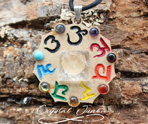 Wood Pendant engraved with Chakra symbols and color stones representing each chakra down around the edges. Centered is a clear quartz   Key: Grounding and Centering, Self Reealization  Wood represents - Trees have roots that grow into the earth for stability and growth. wood stabilizes thoughts for good decision making by grounding the mind. Crystal quartz is used for clarity, focus, and intention of positive admiration. It opens your mind if your stuck in thoughts that are not serving you in a positive way. Clear Quartz is an amplifier of healing energy, meditation, and self realization. It is great to work with on all levels of healing and advancement. The crystal quartz energies are positive and fulfilling! Necklace is chosen, spiritually cleansed and packaged with an abundance of gratitude and high vibe positive energy.