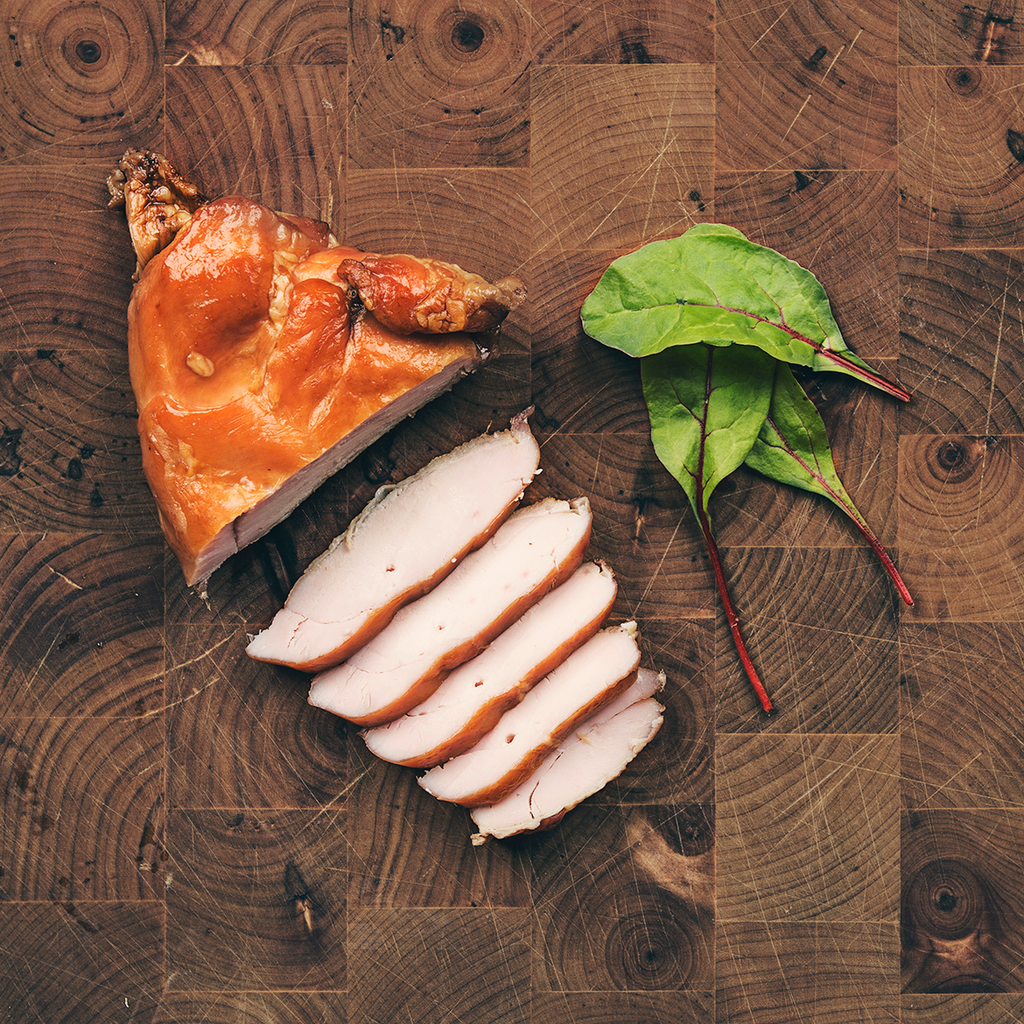 Hot smoked chicken sliced on chopping board