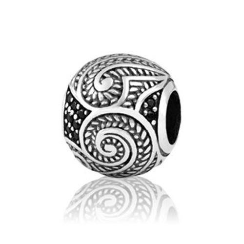 Shining koru (growth) gemstone charm from Evolve New Zealand.