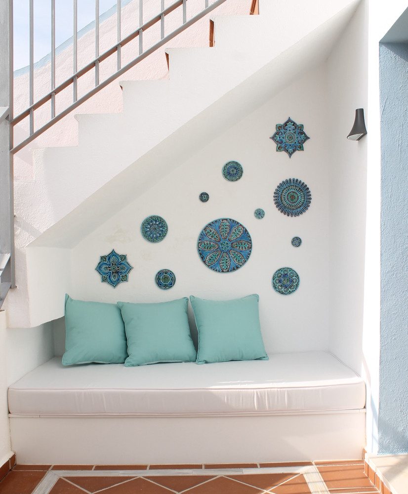 These handmade tiles make a unique wall art installation.  Our decorative tiles are glazed in turquoise and make wonderful outdoor wall art. Perfect for decorating a white wall. Circle garden decor handmade in Spain.