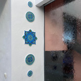 Wall art installation for terrace or outdoor wall art using handmade tiles in turquoise.