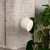 White brick interior with natural decor is illuminated by FLOS AIM pendant lighting by Ronan and Erwan Bouroullec.