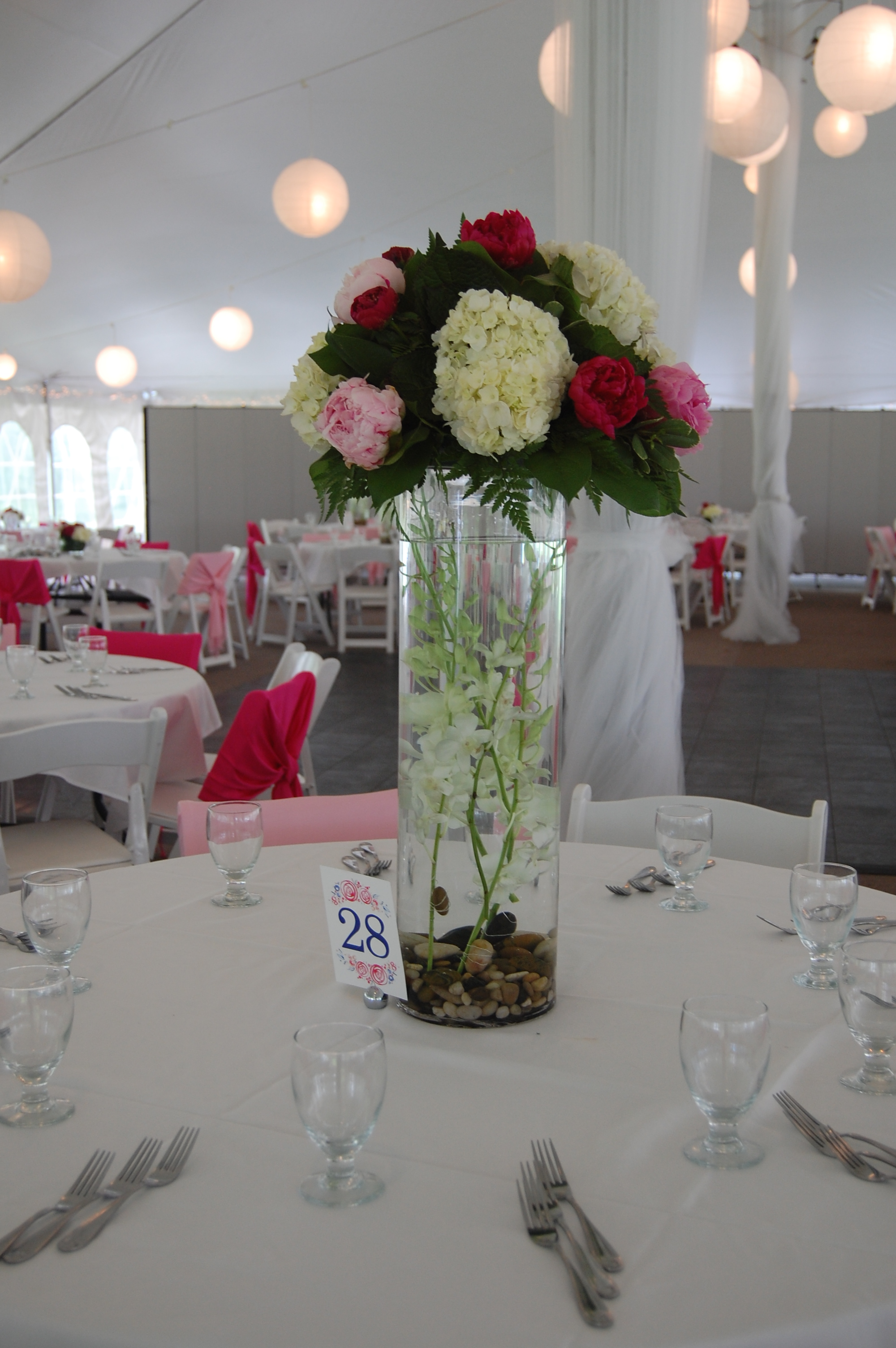 tall cylinder centerpiece with orchids submerges, peonies and hydrangeas on top