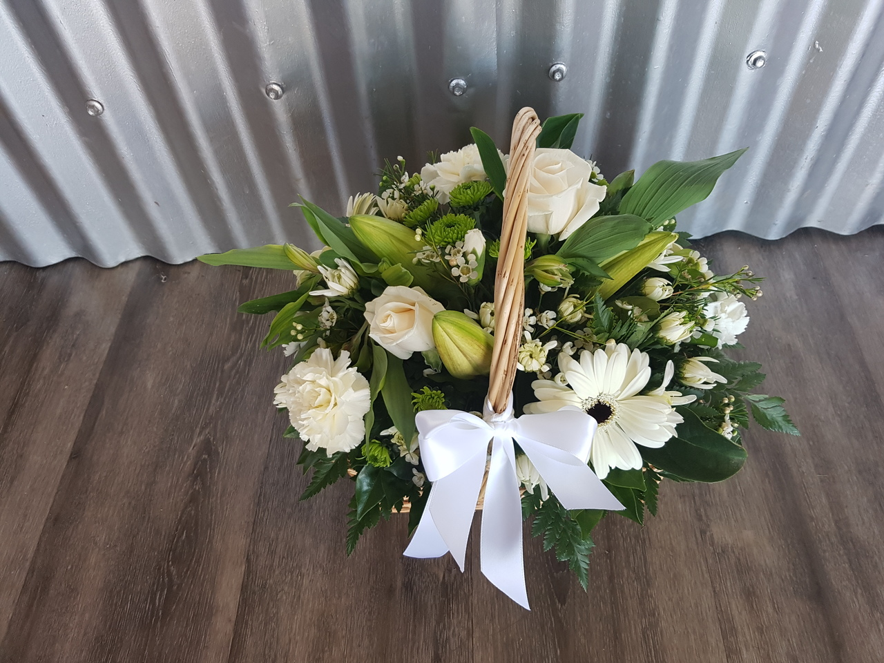 Comfort, a petite basket of mixed blooms in tones of white and green. This arrangement is suitable for delivery to home or funeral service.