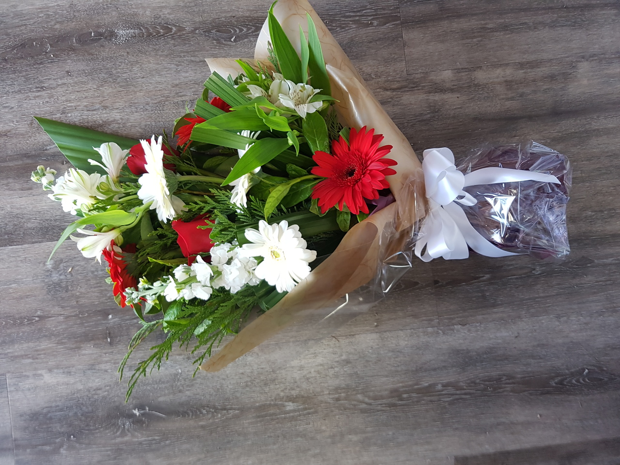 RED AND WHITE FUNERAL SHEAF INCLUDING GERBERAS, ALSTROEMERIA, ROSES AND SNAP DRAGONS.