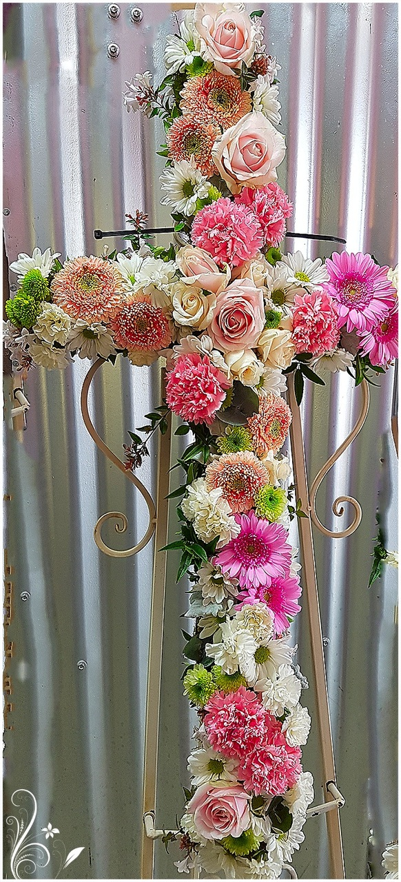 SOFT PINK CROSS ARRANGEMENT INCLUDING GERBERAS, CHRYSANTHEMUMS, ROSES AND CARNATIONS.