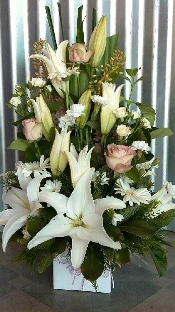 TALL BOX ARRANGEMENT INCLUDING LILIES, ROSES, GERBERAS, SPRAY ROSES AND A VARIETY OF GREENERY.