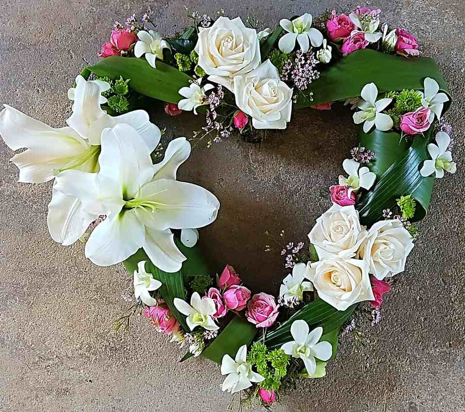 A HEARTFELT WREATH, OF MIXED BLOOMS INCLUDING LILIES, ORCHIDS AND SPRAYROSES.