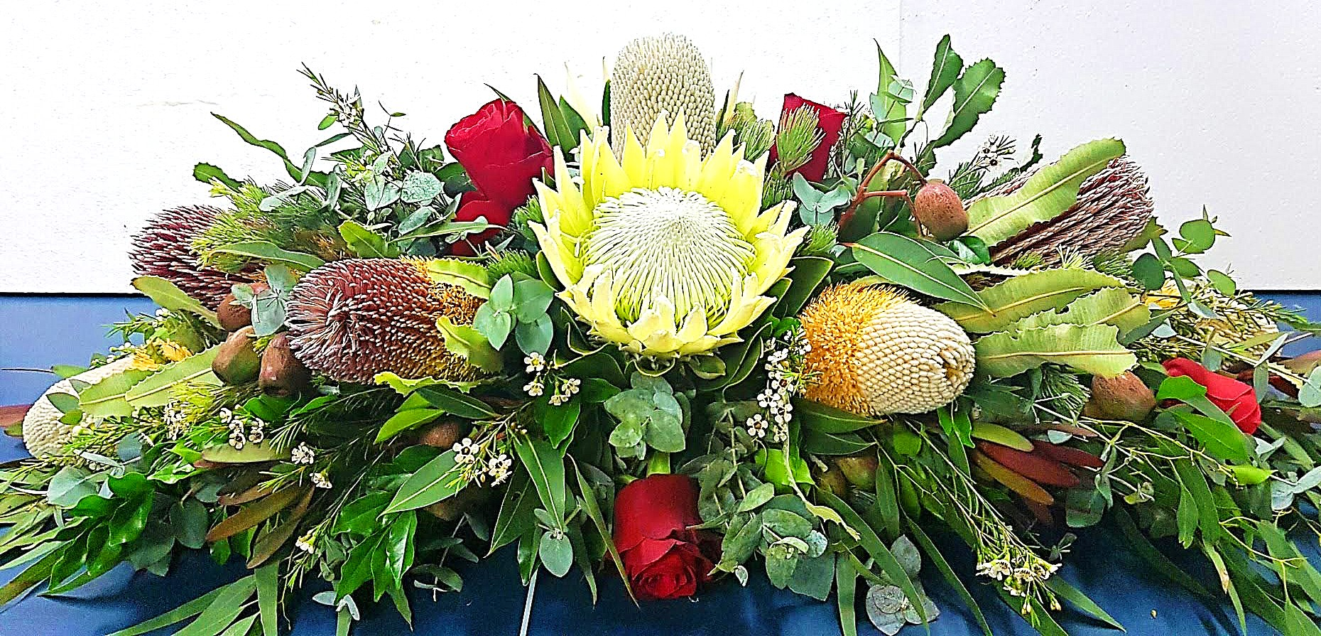 A BUSHMAN STYLED ARRANGEMENT WITH A MIX OF PROTEAS AND BANKSIAS WITH A  SPLASH OF CLASSIC RED ROSES.