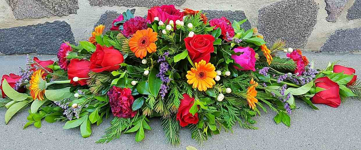 A BRIGHT, COLOURFUL MIX OF BLOOMS INCLUDING ROSES, GERBERAS, BERRIES, EMILLE, AND CARNATIONS.