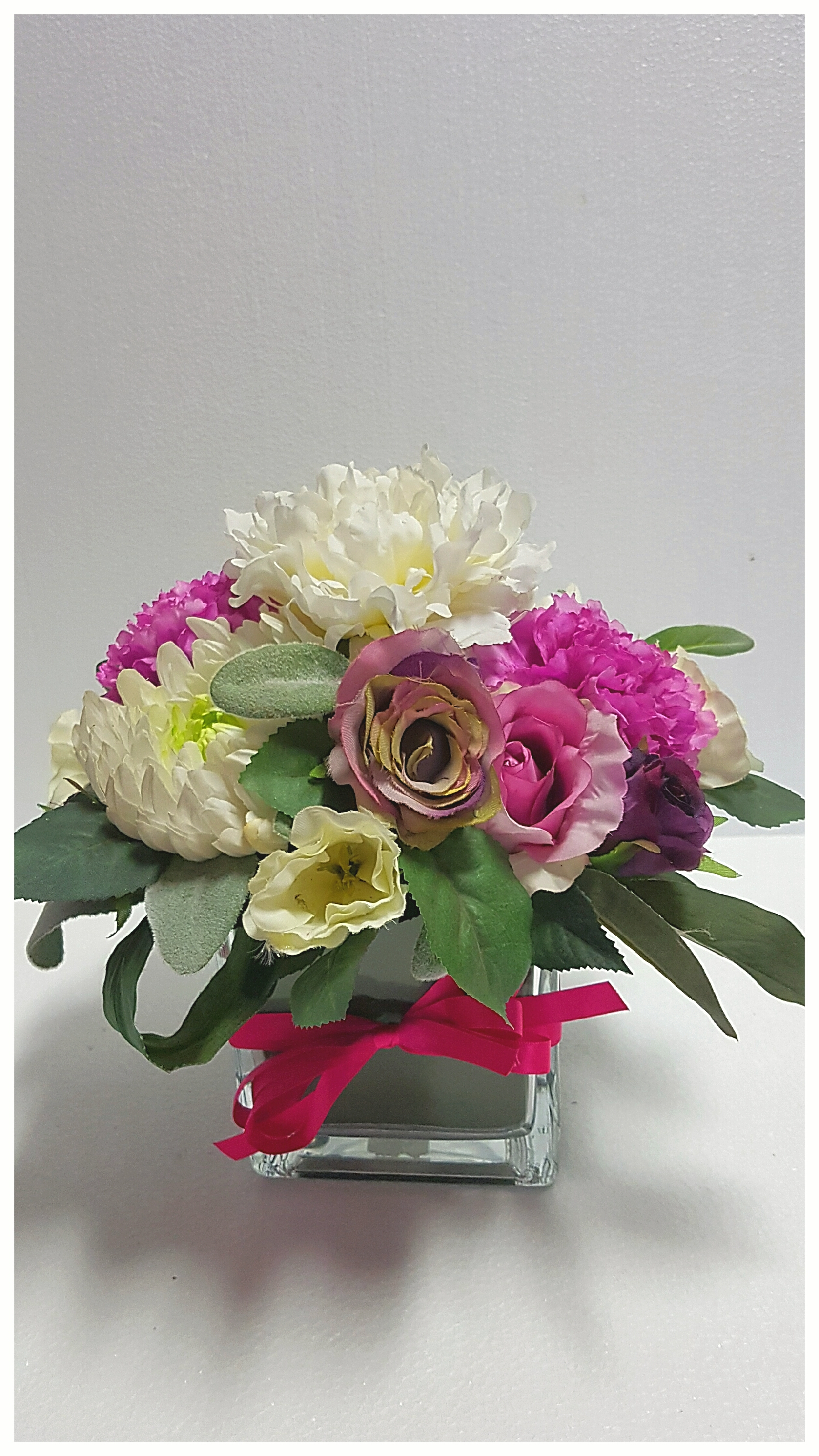 An artificial arrangement of white, pink purple flowers displayed in a glass cube