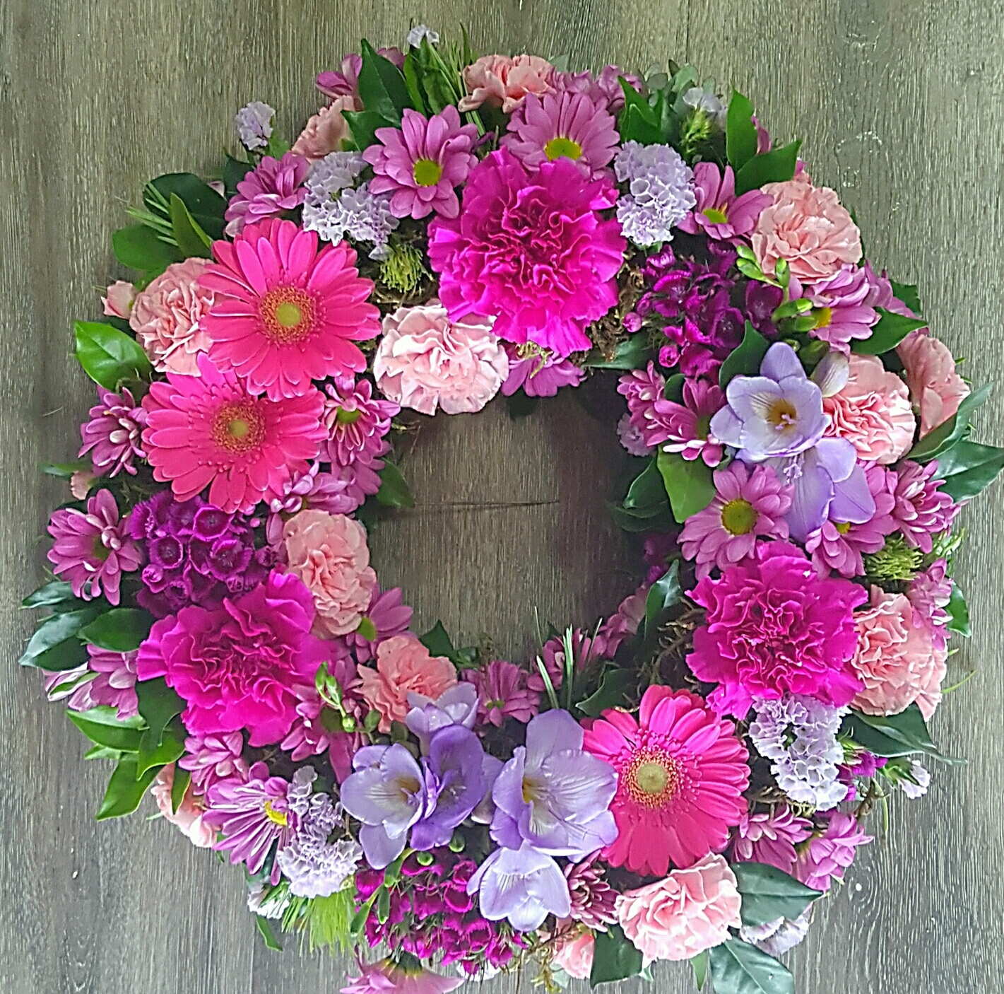 KINDNESS A BEAUTIFUL WREATH OF PINKS AND PURPLES.  SUITABLE FOR A GRAVESIDE SERVICE.