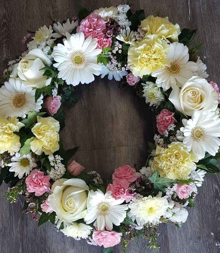 AN ELEGANT WREATH OF BLOOMS IN A PASTEL COLOUR PALETTE, TO HONOUR A LOVED ONE.