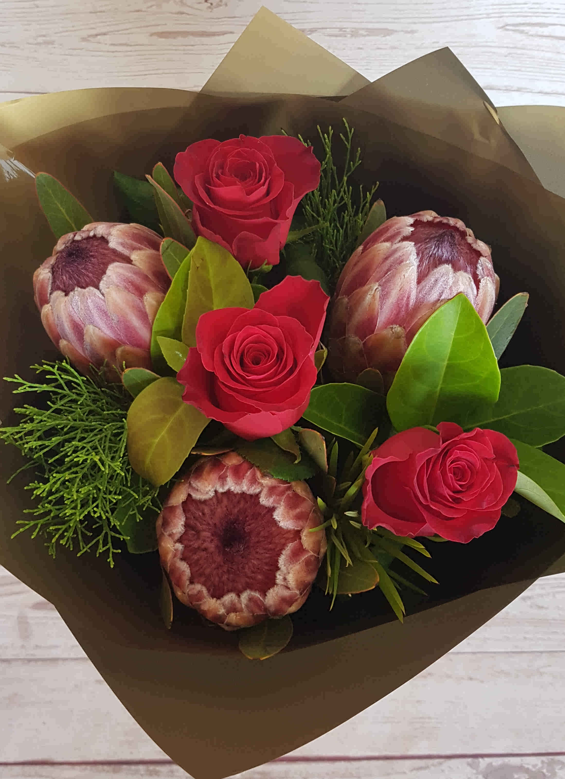 A beautiful  bouquet with the romance of the three red roses, with the added bonus of the pink ice proteas to give longevity.