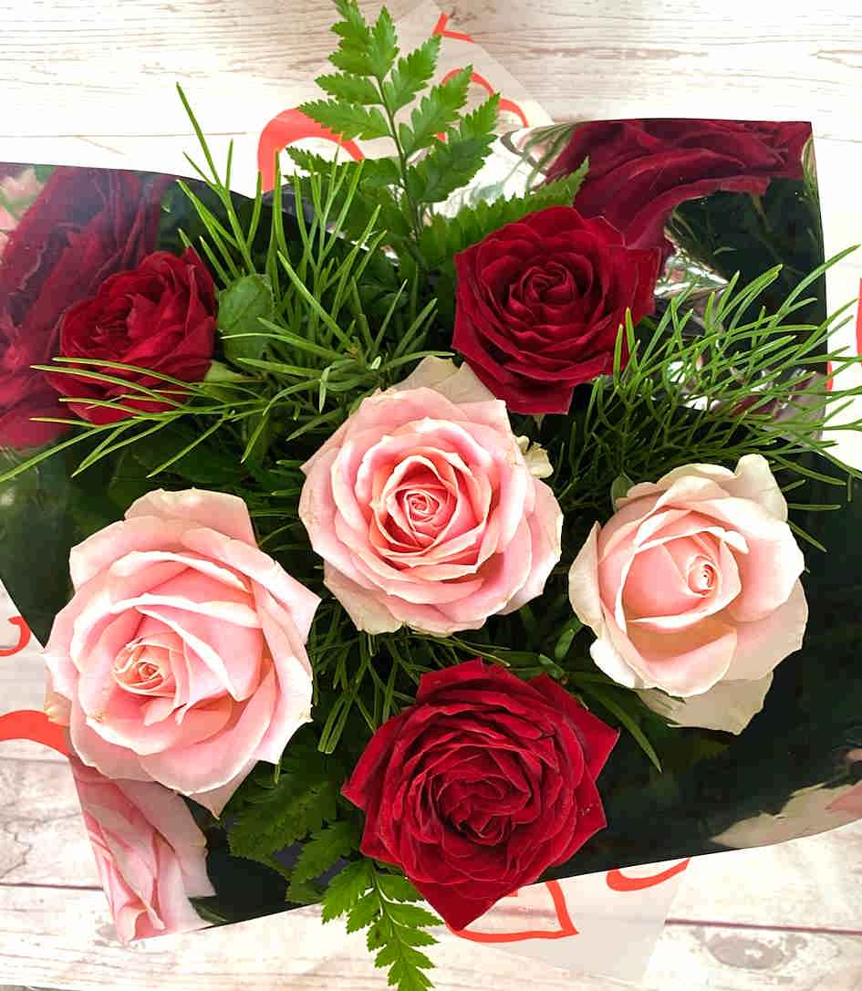 A stunning combination of red roses and soft pink, gift wrapped with foliage