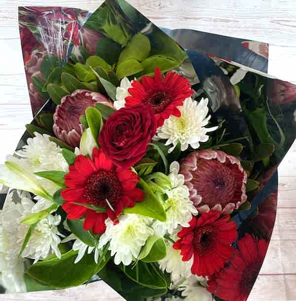 A bunch of lovers blooms, with the longevity of the pink ice proteas, and chryssies, the bouquet also contains gerberas, greenery and a red rose, beautifully gift wrapped.