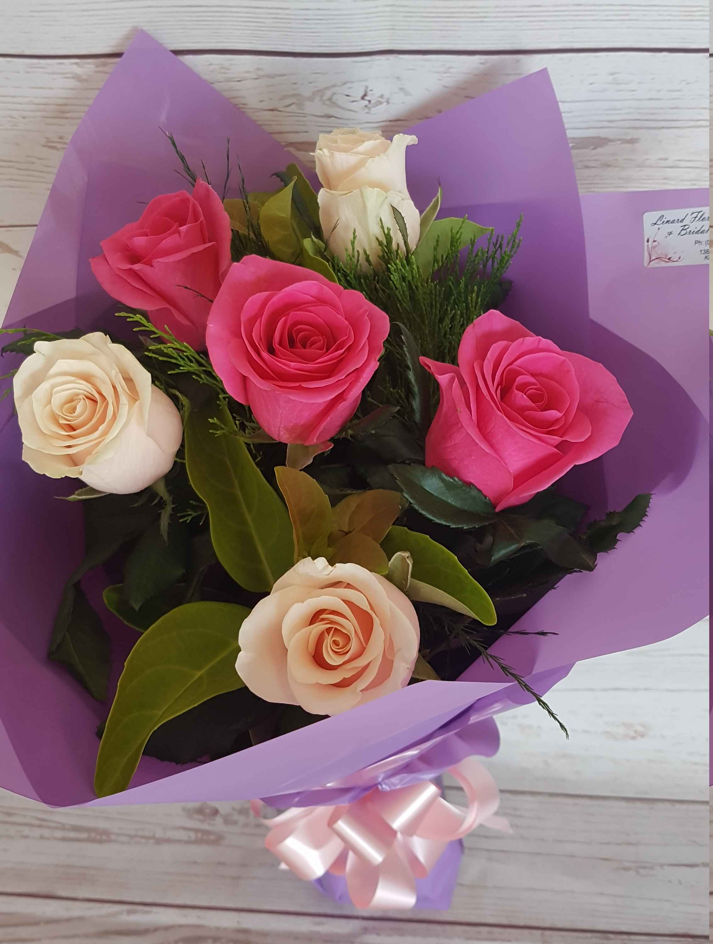 Six beautiful coloured roses with greenery wrapped in a bouquet.