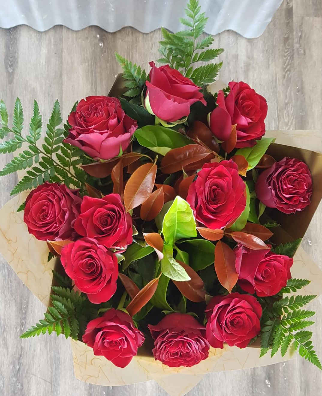 Twelve beautiful red roses with greenery wrapped in a bouquet.
