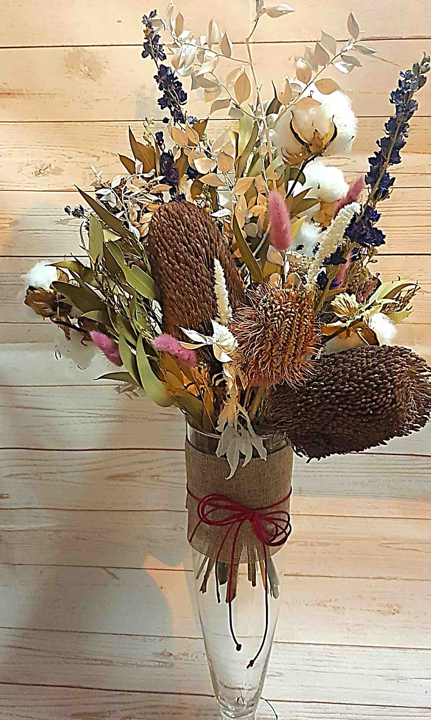 Lily a stunning dried and preserved bouquet presented in a beautiful glass vase. Natural tones with splashes of blue delphinium and blush bunny tails, and who doesn't love cotton, a featured item in this arrangement.