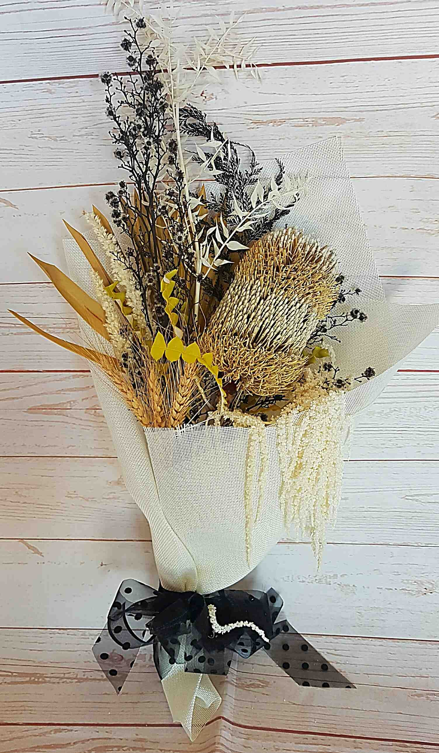 The Audrey bouquet a classic collection of dried and preserved blooms in neutral, white tones with a splash of black.  This bouquet requires no water, and if not placed in the sun will hold its beauty.