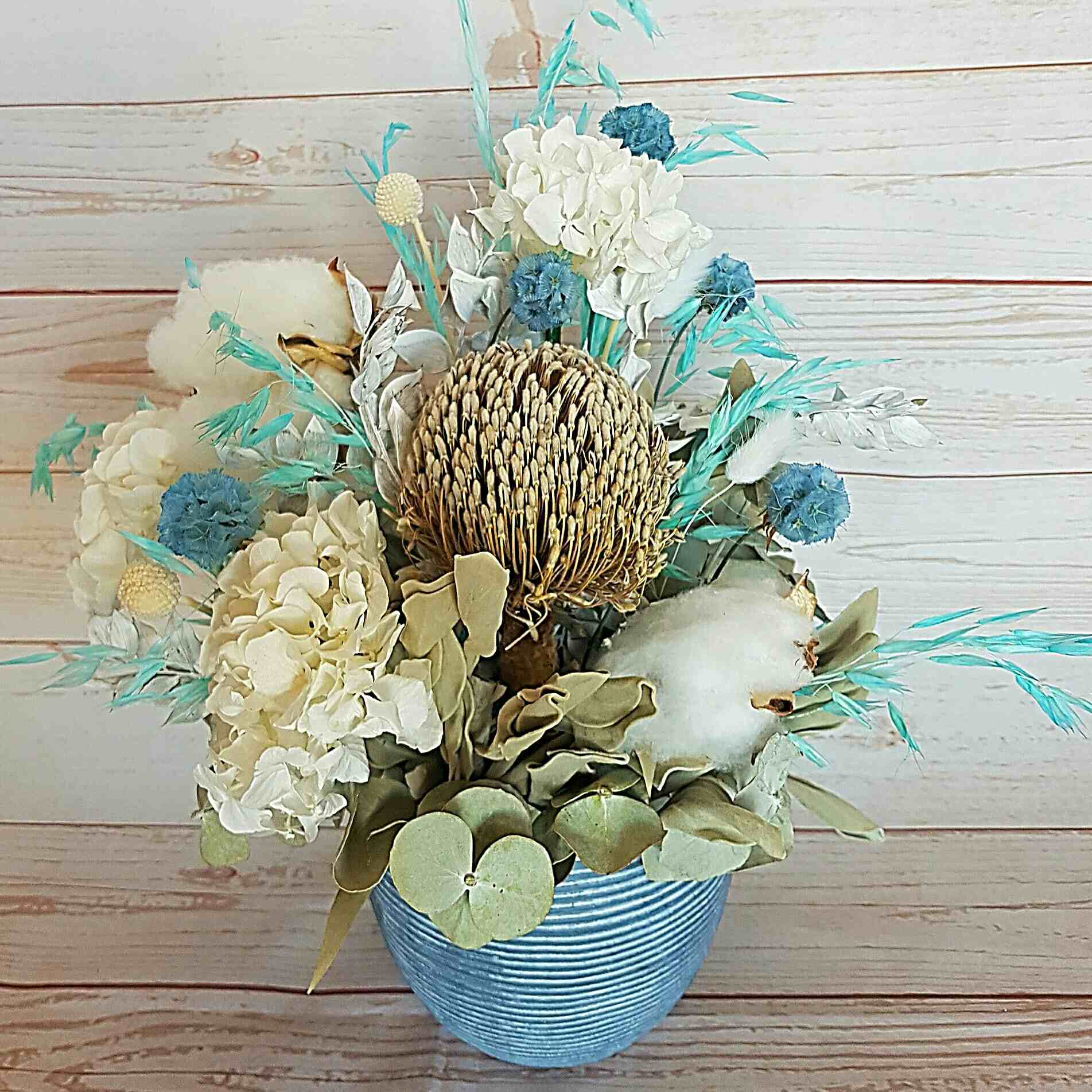 Josh is a soft front facing arrangement of whites, pale blues, neutral, soft tones.  Presented in a ceramic container it is filled with preserved, and dried blooms.  Perfect to celebrate the arrival of a new born, or to adorn an office or bedroom.