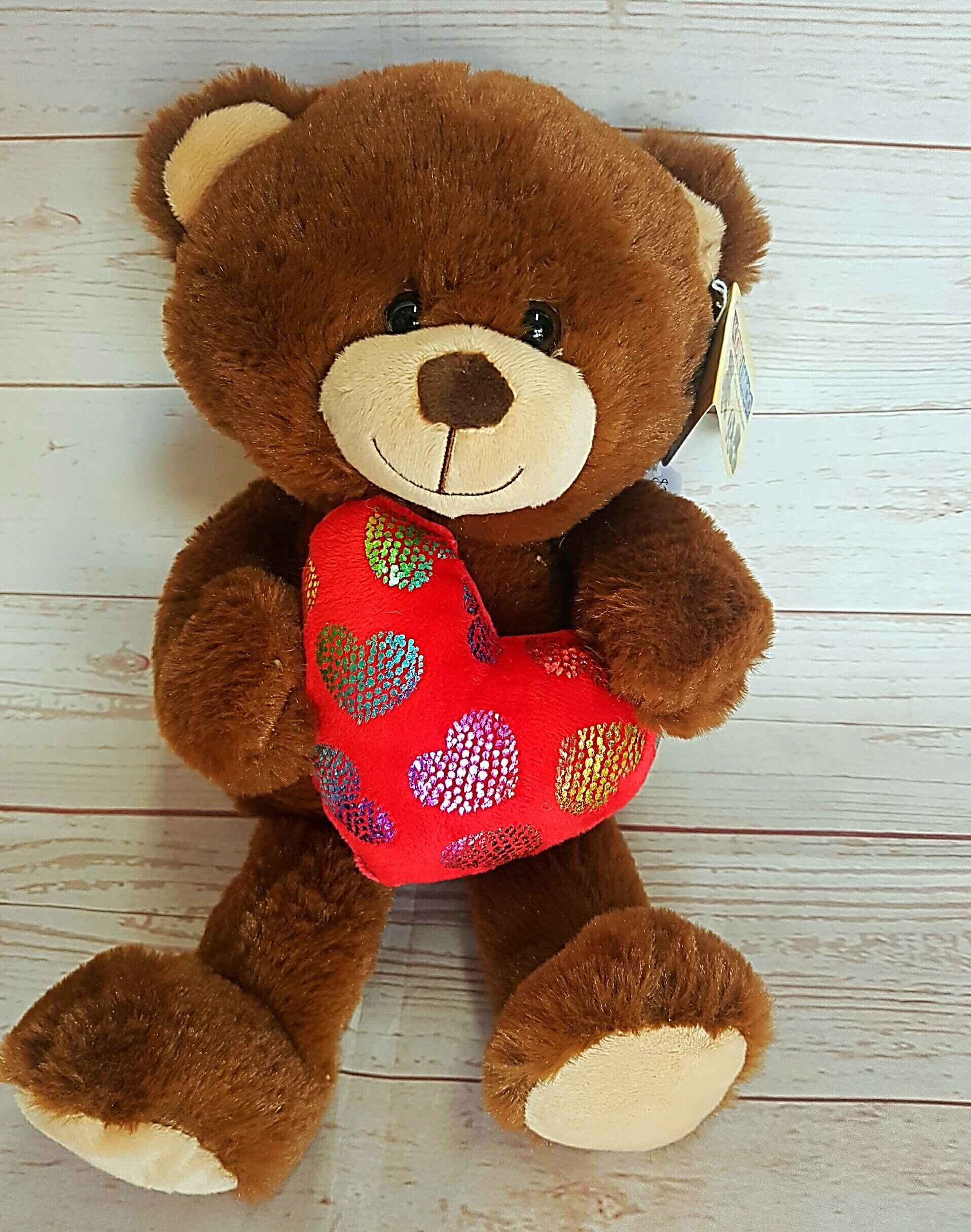 Amore, a soft, cuddly teddy bear holding his heart.  Amore sit 25cm, and will bedazzle his new home.