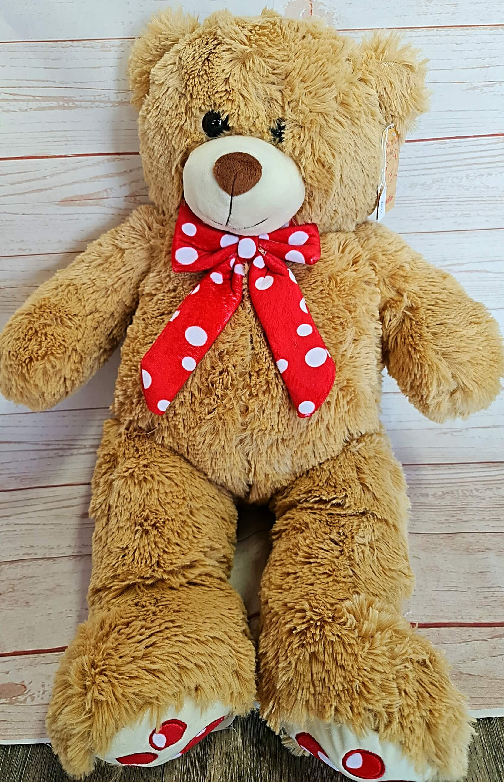 Elijah Brown Bear is a classic design made of soft fluffy fur with a red and white polka dot bow around his neck and matching paw prints on his feet. Elijah sits 66cm tall