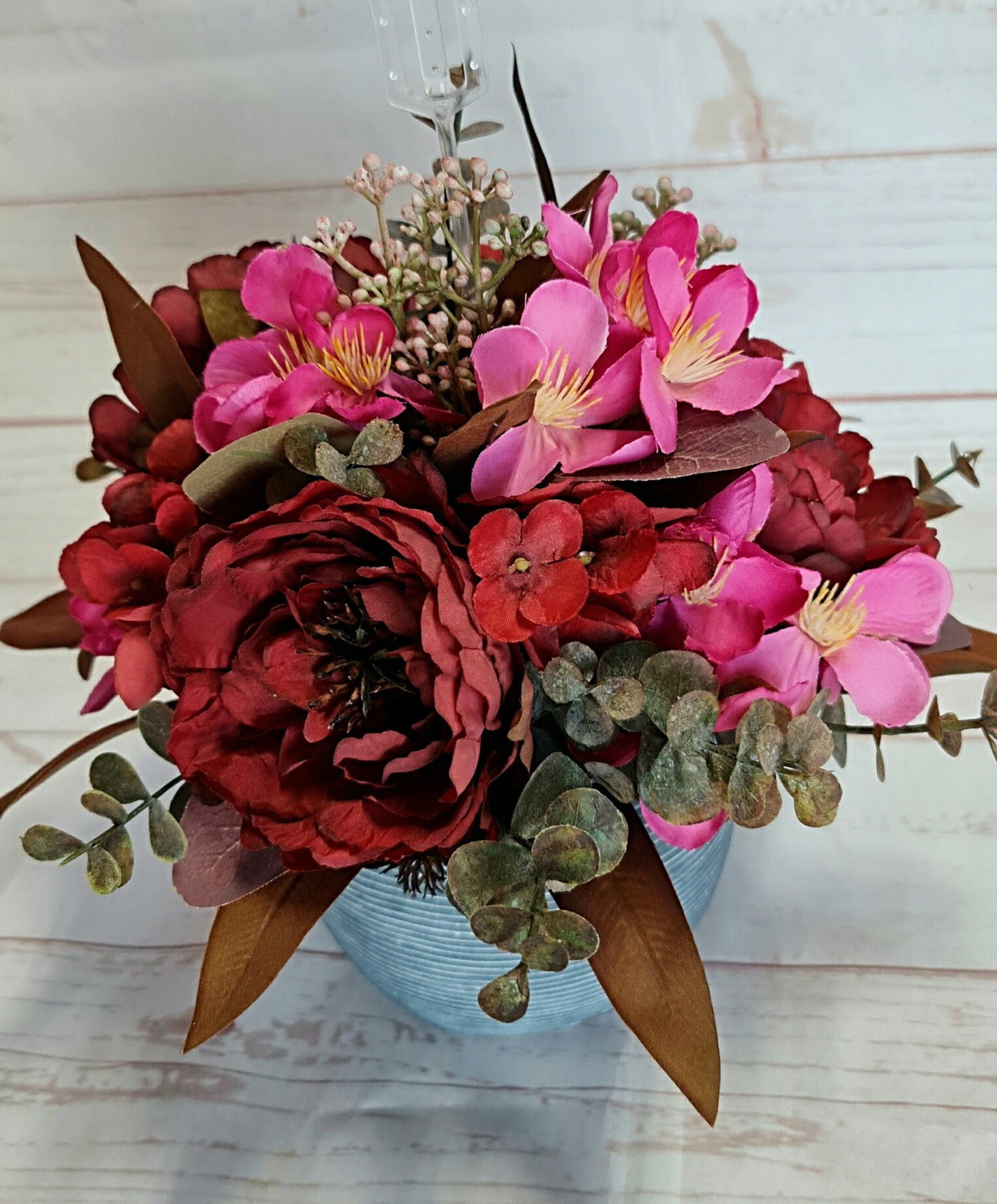 This petite artificial arrangement is a must for any home, office, or hospital.  Contained in a ceramic, artificial flowers in tones of burgundy and pink.