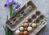 Lifestyle image of an open view style egg carton filled with farm fresh eggs surrounded by purple flowers