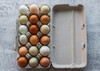 Open brown 18-egg paper-pulp carton filled with multicolored eggs on a wooden table.